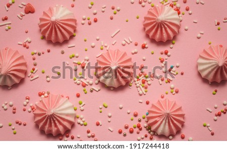Pink and white pastel colored meringues with colorful sweet candy on pink pastel background. Happy birthday greeting card. Sweet candy concept. Banner.                                                  Foto d'archivio ©