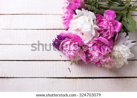 Pink and white peonies flowers on white painted wooden planks. Selective focus. Place for text.