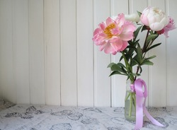 Pink and white peonies in a glass vase on a linen tablecloth, on a white wooden background