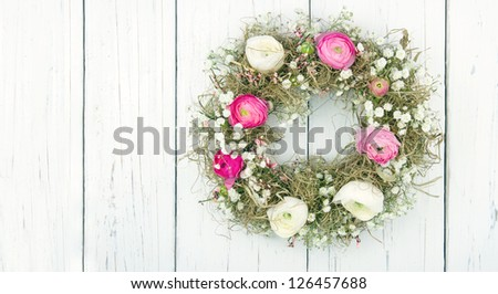 Pink and white summer flower wreath on white wooden rustic background