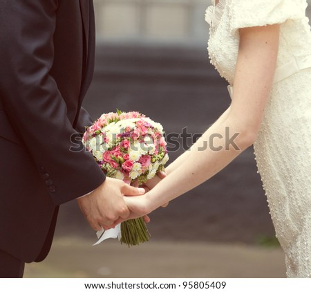 pink and white wedding bouquet in the hands of the bride and groom