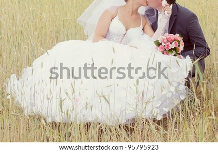 pink and white wedding bouquet of roses in the hands of the bride and groom
