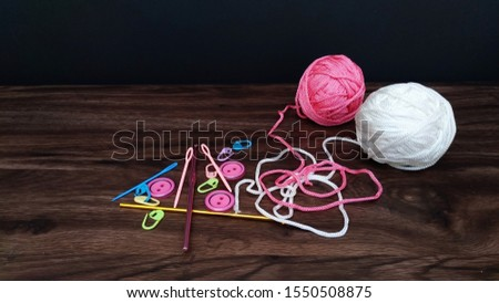 pink and white yarn balls with crocheting accessories. crocheting accessories are hooks,needles and buttons on a wooden table.close up shot