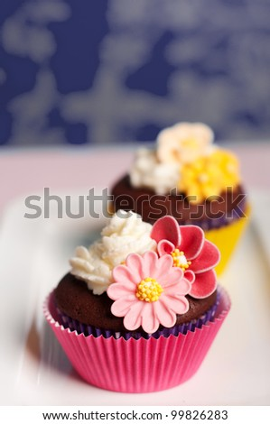 pink and yellow cupcakes decorated with flowers and whipped cream