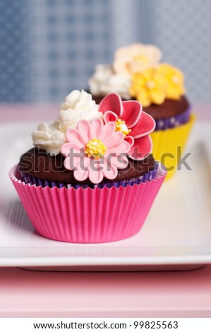 pink and yellow cupcakes with flower decoration