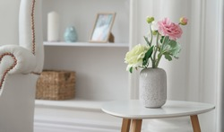 Pink and yellow roses in Modern white vase on white table beside classic armchair