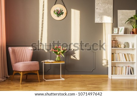 Pink armchair next to a table with red tulips in cozy grey living room interior with decor on the wall