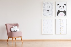 Pink armchair with cloud shaped toy standing in baby room with simple posters on empty wall