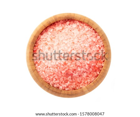 Pink aromatic bath salt in a wooden bowl isolated on a white background, top view.