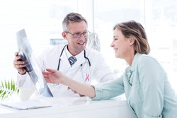 Pink awareness ribbon against doctor having conversation with his patient and holding xray