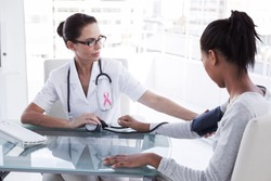 Pink awareness ribbon against doctor taking patients blood pressure