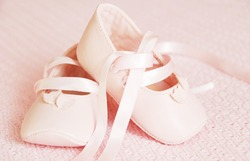Pink baby girl shoes on the pink blanket