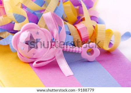 pink baby rattle on pastel tissue paper with ribbon