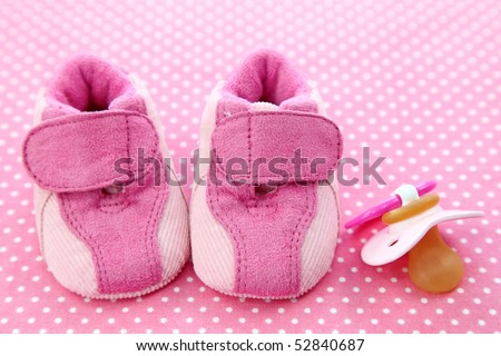Pink baby shoes and dummy on spotted background