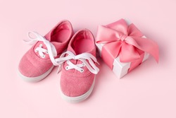Pink baby shoes and gift present box, concept of first steps, birthday, baby shower, expectation, pregnancy, maternity, motherhood, parenthood. Monochrome card for baby shower party, copy space