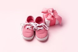 Pink baby shoes and gift present box, concept of first steps, birthday, baby shower, expectation, pregnancy, maternity, motherhood, parenthood. Monochrome card for baby shower party