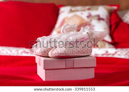 Pink Baby Shoes On Pink Gift Box In Red Bed