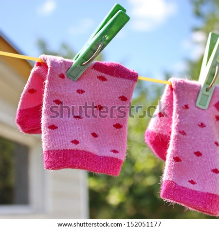 Pink baby sock hanging on the clothesline outdoor