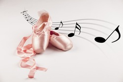 Pink Ballet shoes on white background with musical notes in the background.