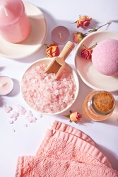 Pink bath salt and body care products with pink roses. Beauty treatment. Spa relax concept. Top view.