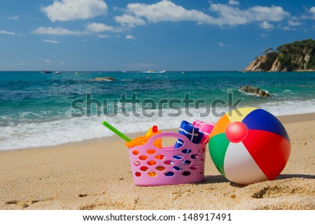 Pink beach bag and colorful ball in the sand near the water line at the Spanish beach