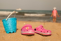 Pink beach crocs and blue sand toys on sandy beach.Beach flip flops in the foreground and blurred sea in the background.