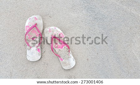 pink beach sandals on sand beach background with space for adding text