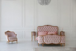 pink bed and chair in the art deco style in the white bedroom interior