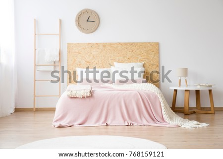 Pink bedsheets on king-size bed next to a ladder and lamp on a table against white wall with DIY clock