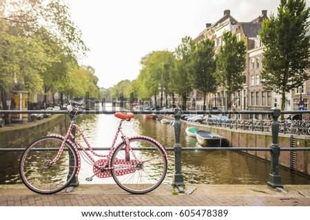 pink bicycle on a bridge among...