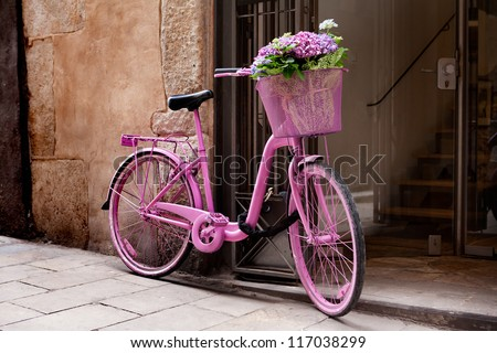 pink bicycle standing on the street - some flowers in the basket