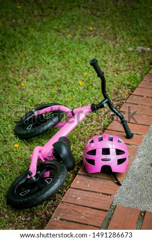 Pink bike for little girl. A pink bike parking in the park near the pavement with safety headgear, helmet on the side.