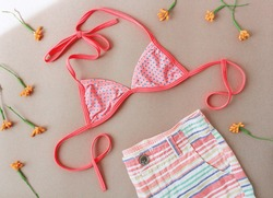 Pink bikini top with pants above neutral background with yellow flowers. Stylish swimwear set. Top view image