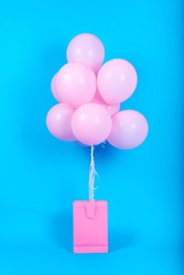 Pink birthday air balloons in blank pink shopping bag on blue background, copy space for text. Pink balloons in blank paper bag, free space. Valentine, birthday concept. Happy holiday flying balloons