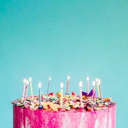 Pink birthday cake over blue background