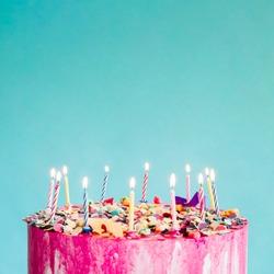 Pink birthday cake over blue background