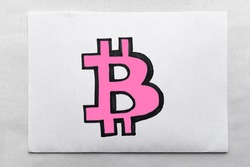 pink Bitcoin Sign Drawn on White Paper. Virtual cryptocurrency concept. Marker-drawn bitcoin symbol on the white paper