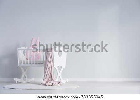 Pink blanket and pillow in white cradle against a wall with copy space in white baby\'s bedroom interior with rug
