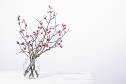 pink blossoming peach flower branches at simple old glass jar on white wooden table