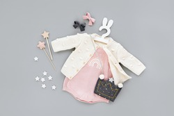 Pink bodysuit with knitted jumper, kids handbag shape of crown on cute hanger with bunny ears. Set of  baby clothes and accessories  on gray background. Fashion childs outfit. Flat lay, top view