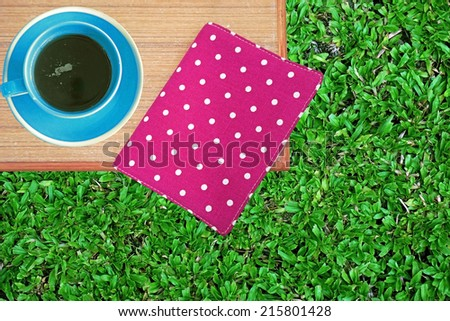 Pink book on table with coffee cup on green grass