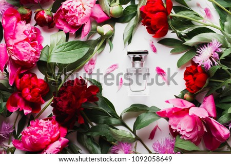 Pink bottle of women's perfume next to the flowers of peony. Spring gentle fragrance for women. Top view, flat lay