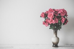 Pink bouquet of azalea in clay vase on table at gray wall. Empty place for inspirational, emotional, sentimental text, quote or sayings. Front view.