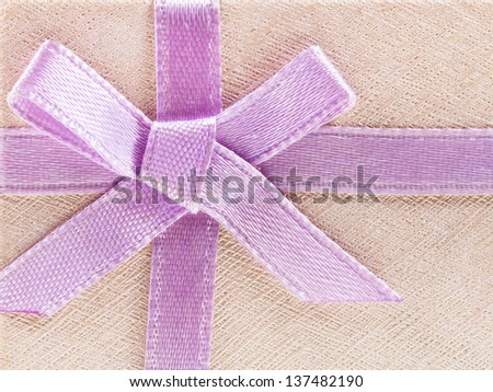 pink bow on shining paper gift box close up