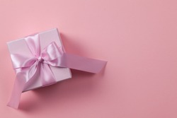 Pink box with ribbon and bow on a paper background with space for text