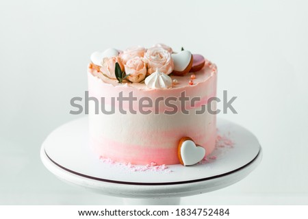 Pink cake decorated with pink rose flowers and merengue cookies on the white background. Happy Valentine's day cake. Wedding pink cake on the white cake stand