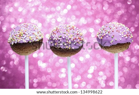 Pink cake pops decorated with colorful sprinkles. Pink glittering background, very festive.