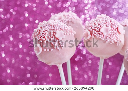 Pink cake pops decorated with sprinkles. Pink glittering background