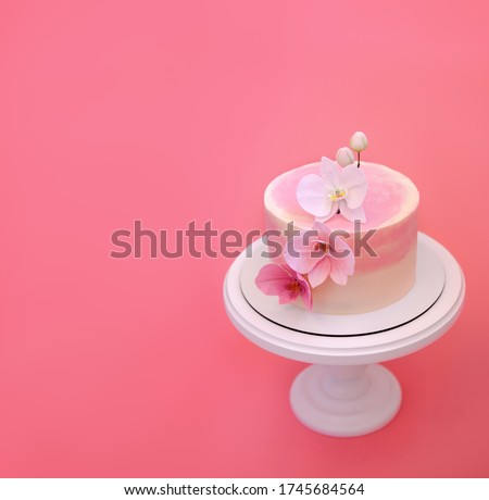 Pink cake stands on a round white stand on a pink background. Cake decorated with sugar flowers orchids. Beautiful dessert decorated with flowers. Foto stock ©