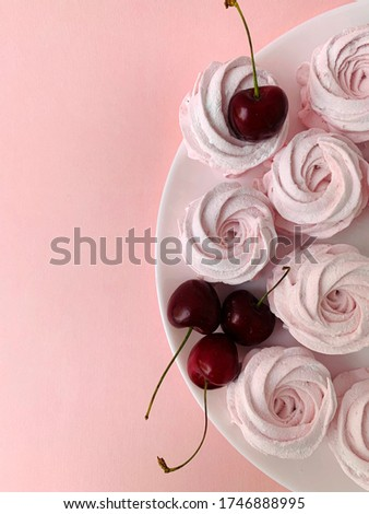 Pink cakes and cherries on a white plate. Light and airy dessert. Mobile photo.